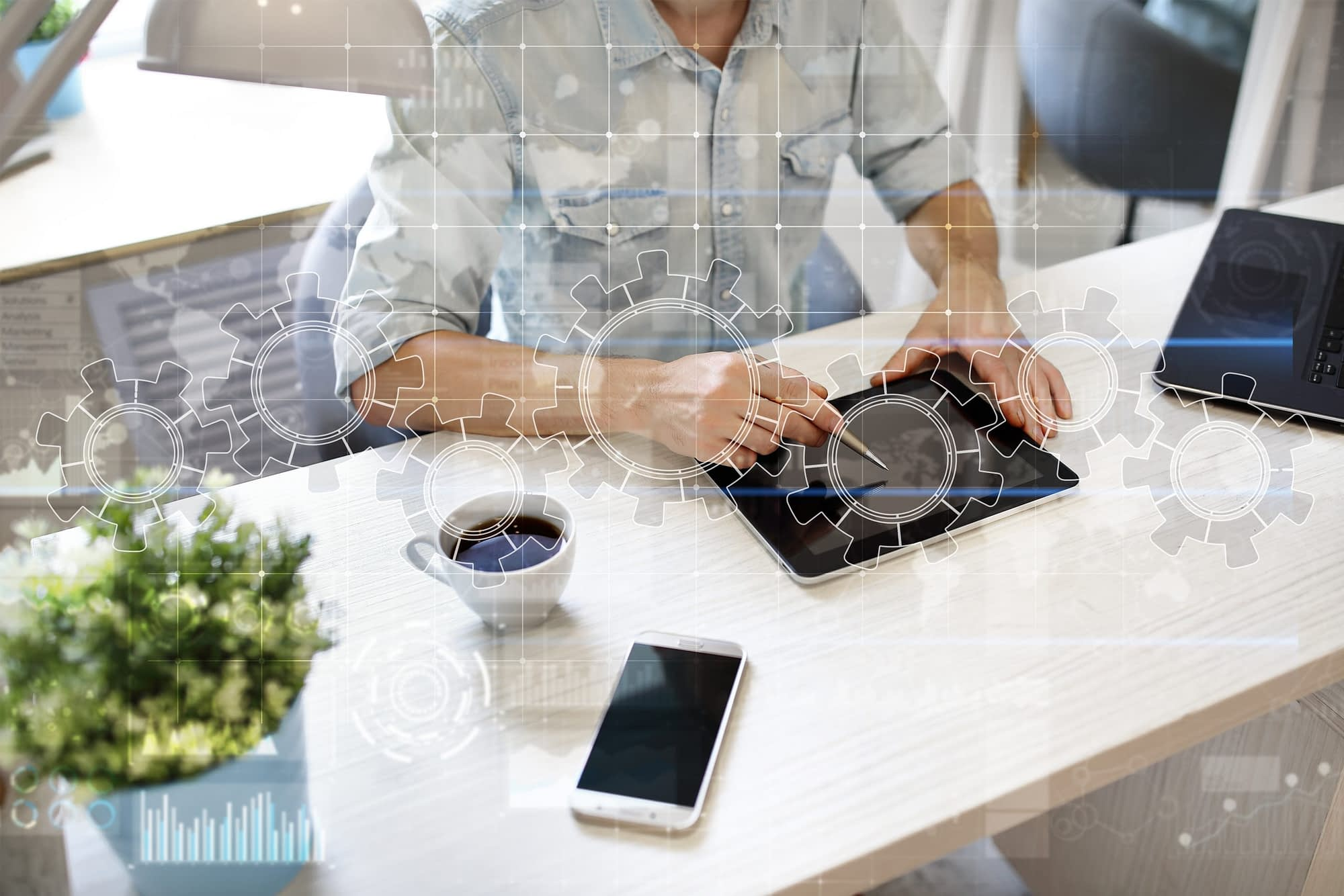 Small business operations manager sitting at desk on tablet with a cog and gear image overlay.