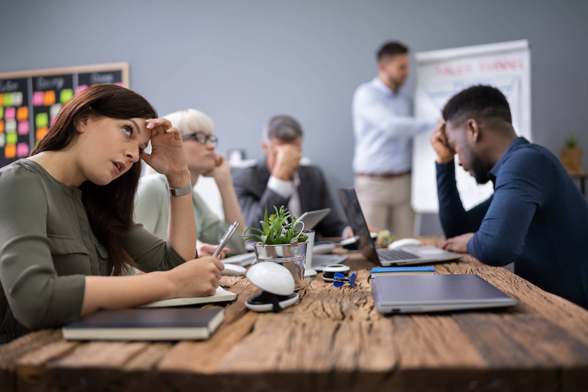 Business team sitting in a meeting look like they need culture change management.