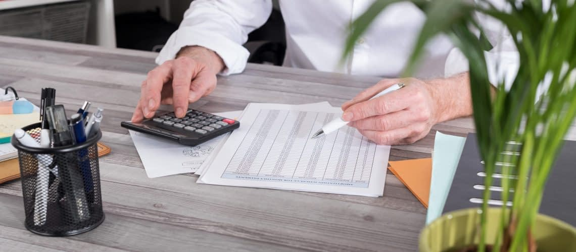 Businessman doing his small business accounting with a calculator sitting at desk.